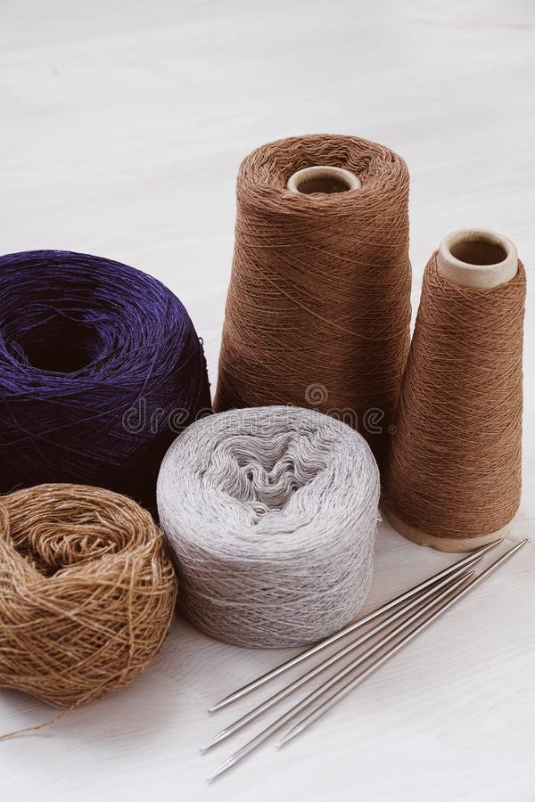Multicolored threads, skeins and tangles of Italian wool yarn, knitting needles on a white  background. The concept of knitting, needlework, handmade stock image