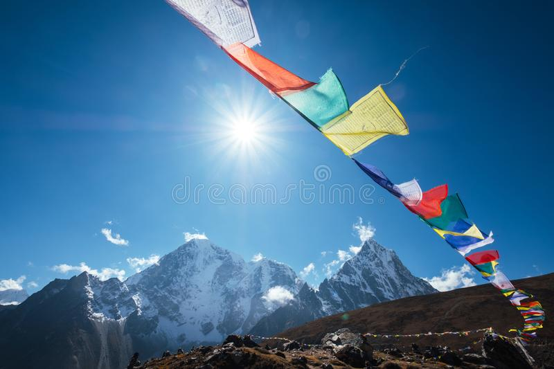 Multicolored Tibetan prayer flags with mantras flapping on the wind with High Himalayas range background. Taboche 6495m and royalty free stock photo