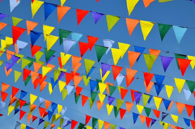 Multicolored triangular small flags to celebration party against blue sky as a background.Street holiday concept. royalty free stock images