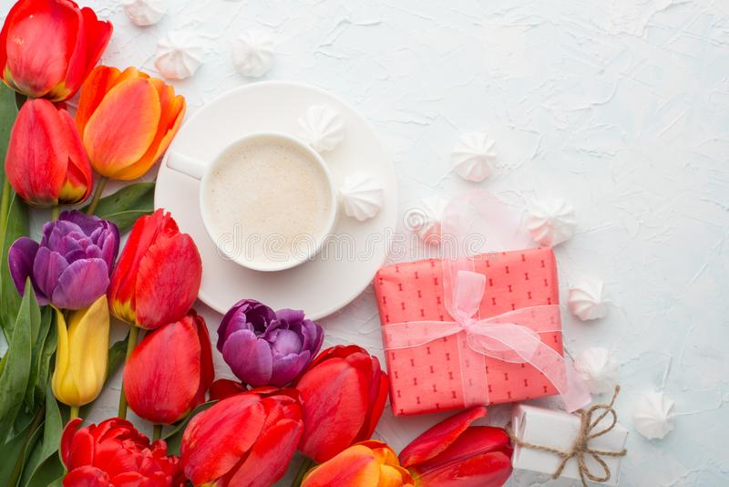 Multicolored tulips with coffee, gifts and a bise on a light background, top view, with empty space for writing or advertising royalty free stock photo