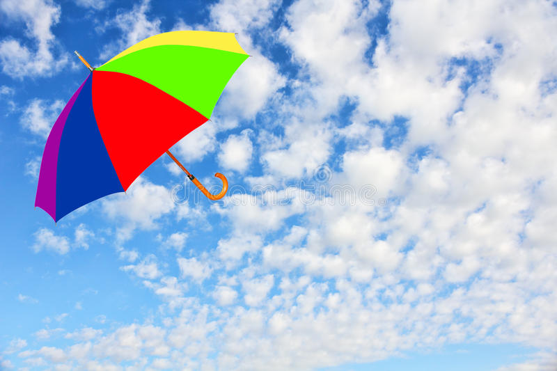 Multicolored umbrella flies in cloudy sky.Wind of change concept. royalty free stock photos