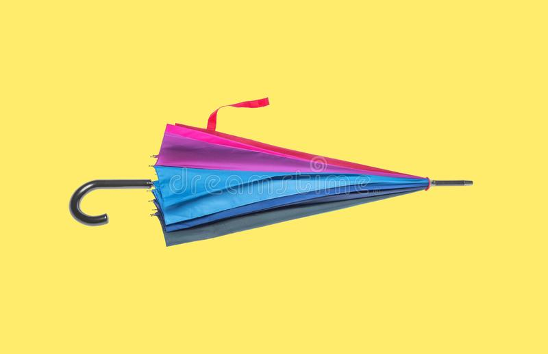 Multicolored umbrella on a yellow background. Multicolored cool umbrella on a yellow background royalty free stock photography