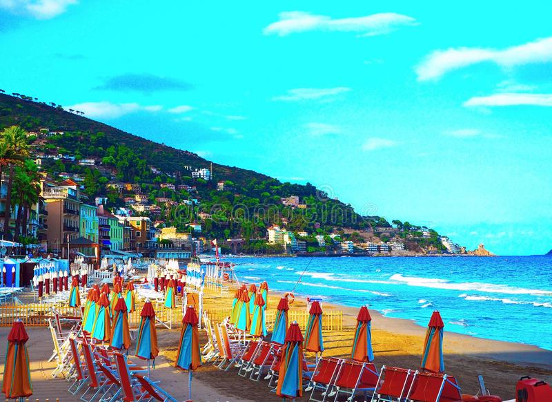 Multicolored umbrellas on the beach in Alassio, province of Savona, Sanremo region, Italy. City at sunset royalty free stock photos