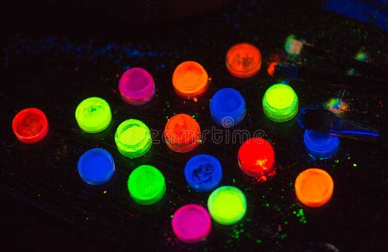 Multicolored UV powder in containers on the black background. stock image