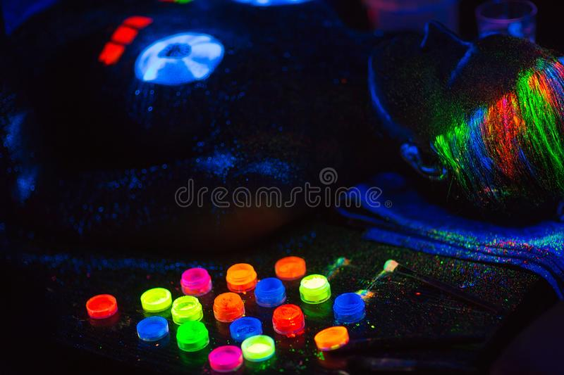 Multicolored UV powder in containers on the black background. Multicolored UV powder in containers stock photos