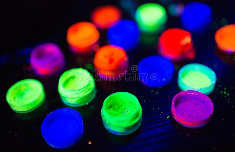 Multicolored UV powder in containers on the black background. Multicolored UV powder in containers royalty free stock image