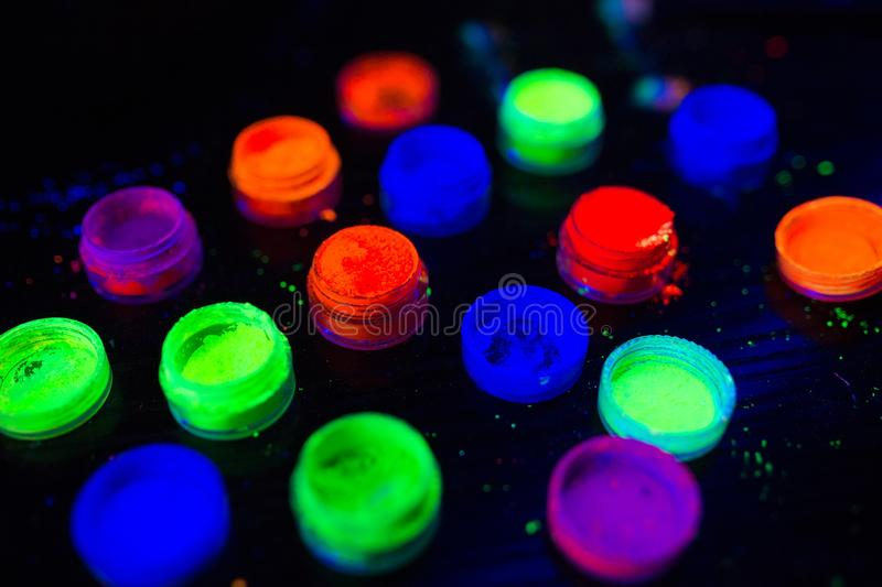 Multicolored UV powder in containers on the black background. Multicolored UV powder in containers royalty free stock photos