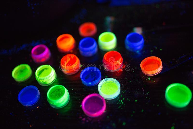 Multicolored UV powder in containers on the black background. Multicolored UV powder in containers stock photo