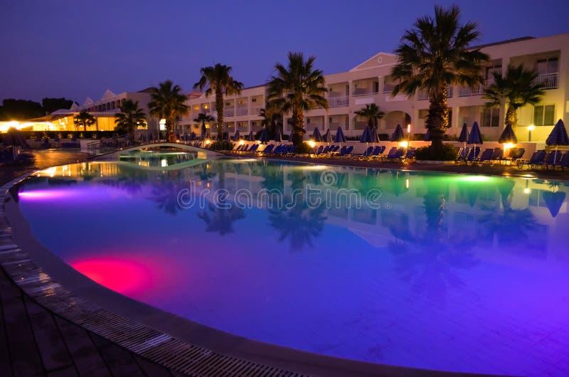 Multicolored verlicht zwembad bij hoteltoevlucht in Griekenland, Korfu tijdens nacht royalty-vrije stock foto's