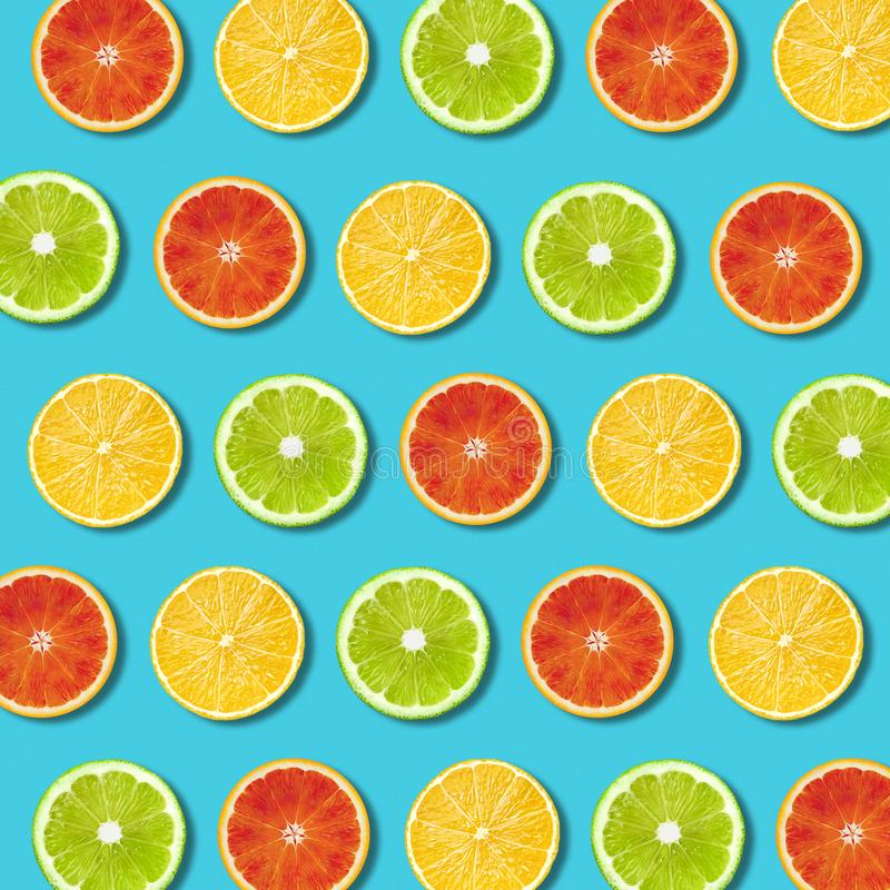 Multicolored vibrant citrus fruit slices texture on turquoise background royalty free stock photos