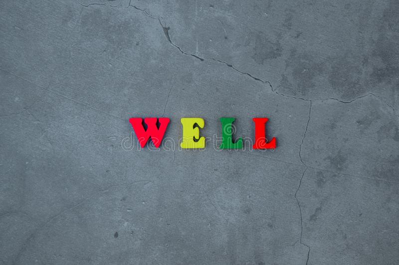 The multicolored well word is made of wooden letters on a grey plastered wall background.  royalty free stock photo