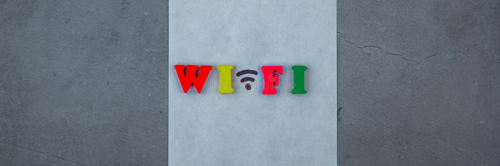 The multicolored wi-fi word is made of wooden letters on a grey plastered wall background.  stock photo