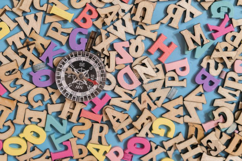 Multicolored wooden letters of the English alphabet on a blue background and compass. Concept search words and search for purpose. In life stock photo