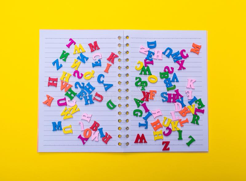 Multicolored wooden letters of the English alphabet. Lie on an open notebook in a line, top view stock image