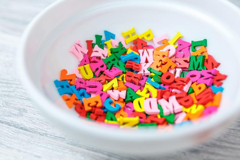 Multicolored wooden letters in a plate, eating knowledge. English letters dyeing in different colors stock photography