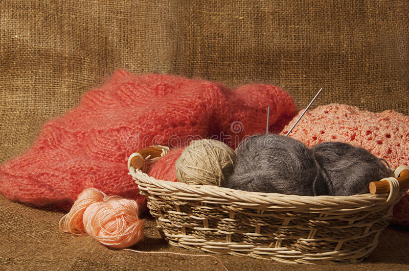 Multicolored yarn balls in a straw basket on the sacking. Knitting. Balls of yarn and fabric stock photos