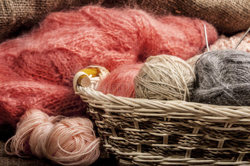 Multicolored yarn balls in a straw basket on the sacking. Knitting. Balls of yarn and fabric stock images