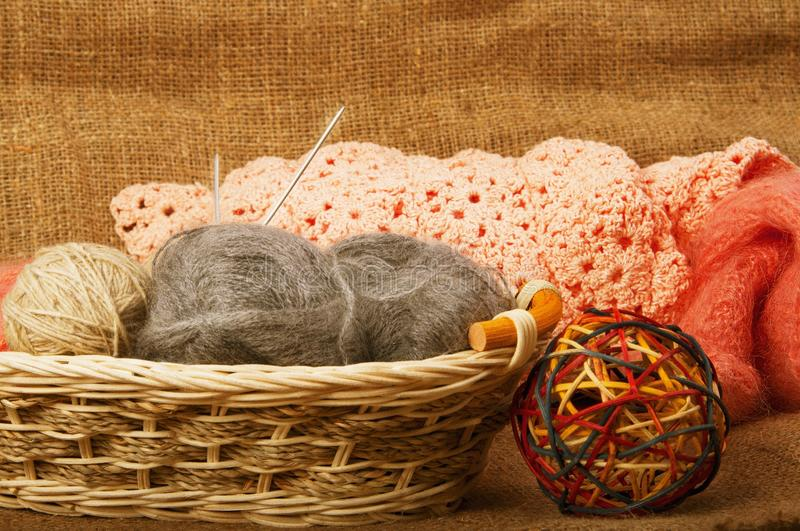 Multicolored yarn balls in a straw basket on the sacking. Knitting. Balls of yarn and fabric royalty free stock photo