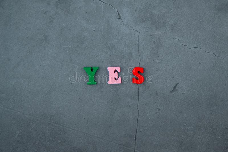 The multicolored Yes word is made of wooden letters on a grey plastered wall background.  royalty free stock photos