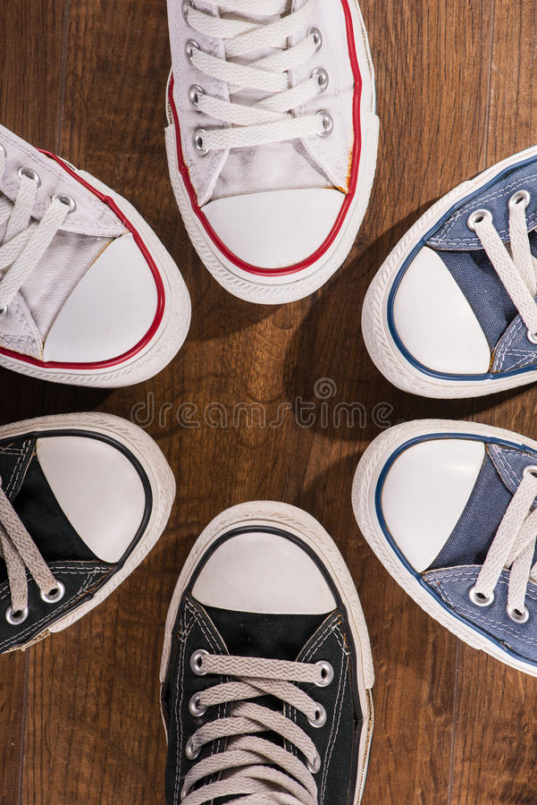 Multicolored youth gym shoes on floor. Cool youth white blue black gym shoes standing in circle on brown parquet wooden floor top view royalty free stock images