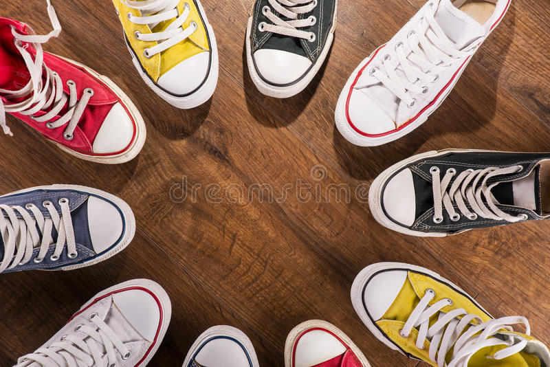 Multicolored youth gym shoes on floor. Cool youth white yellow red blue black gym shoes standing in circle on brown parquet wooden floor with copy place top view stock photo