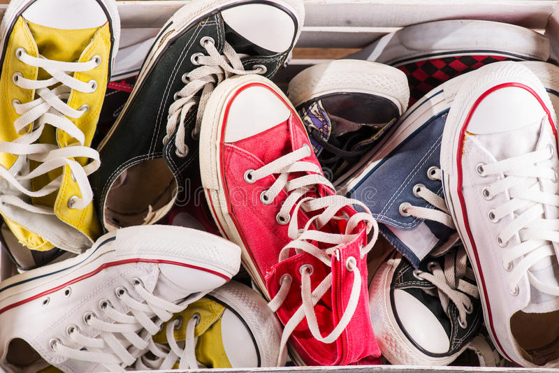 Multicolored youth gym shoes on floor. Heap of several pairs of cool youth red blue white yellow gym shoes on brown wooden floor stock photos