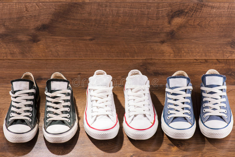 Multicolored youth gym shoes on floor. Three pairs of cool youth white gym shoes with red stripes on brown wooden floor standing in line with copy place top view stock photo