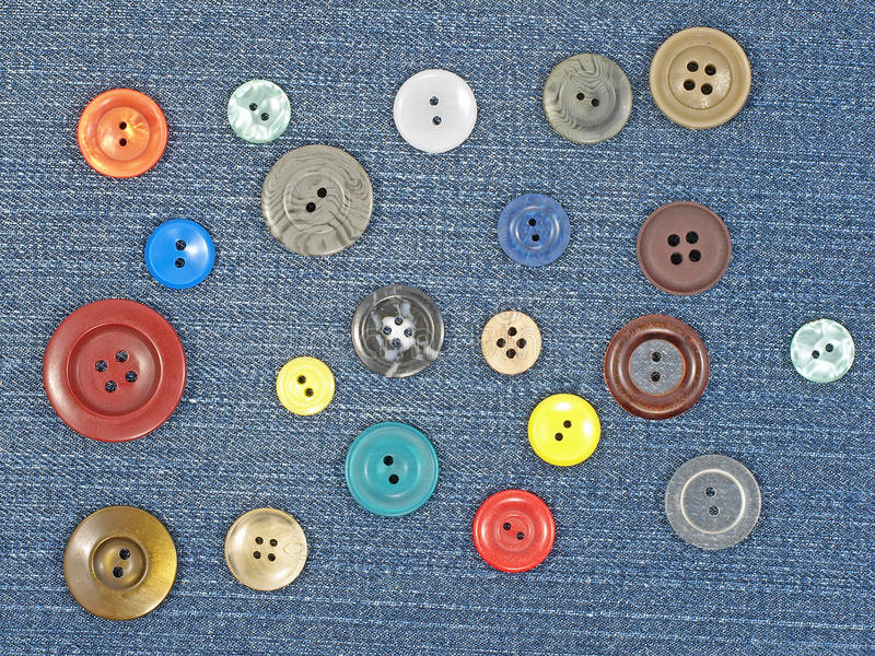 Multicoloured buttons. Various sized multicoloured buttons on blue fabric as background royalty free stock photos