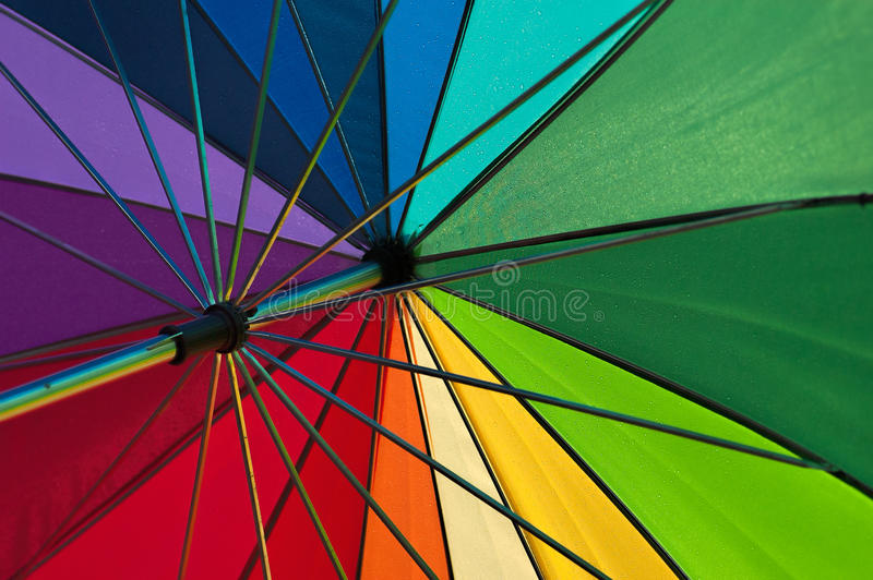 Multicoloured golf umbrella after the rain. Multicoloured golf umbrella shot through after the rain, with sun shining. Angled so that all colours can be seen royalty free stock photo