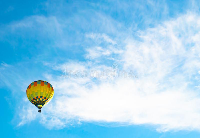 Multicoloured Hot air ballon and clouds. Multicoloured hot air balloon on a background of bright blue sky with white fluffy clouds stock photos