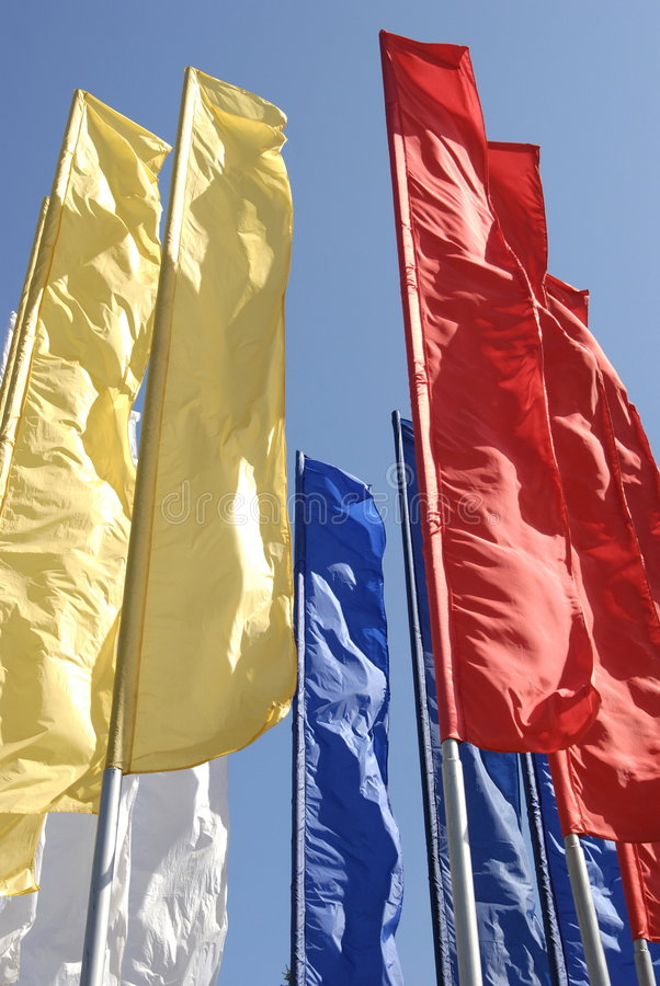 Multicoloured narrow long flags against blue sky. Multicoloured narrow long flags, flying colors royalty free stock photography