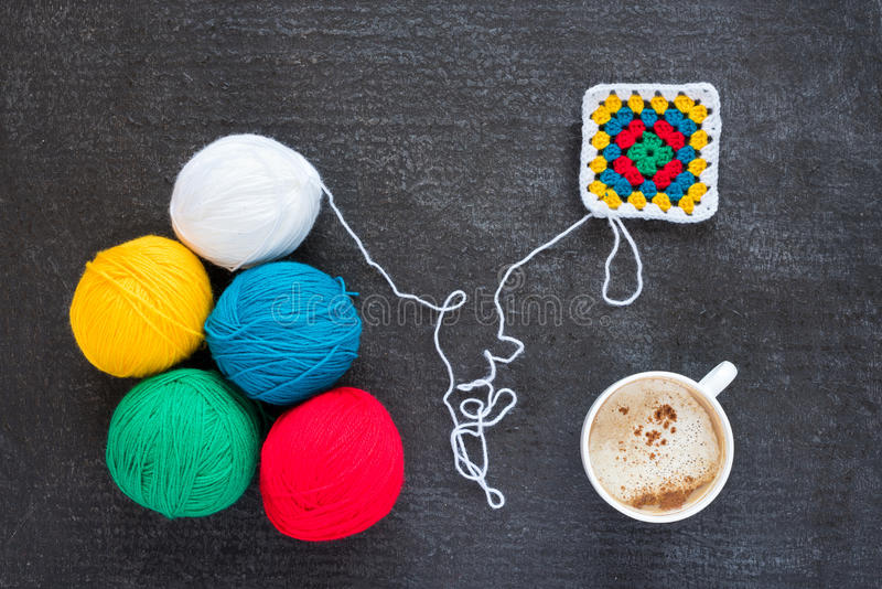 Multicoloured yarn, a crocheted motif and coffee. Balls of multicoloured yarn, crocheted motif and a cup of coffee on grunge black background stock photos