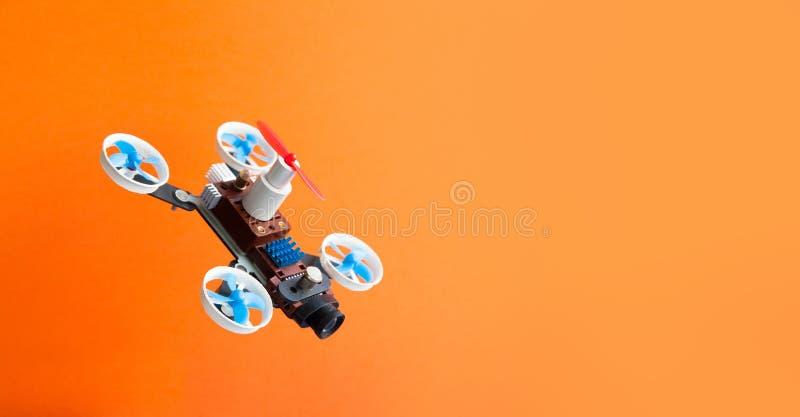 Multicopter del fuco con la macchina fotografica su fondo arancio Eliche robot aeree del meccanismo 5 del rotorcraft di progettaz fotografie stock libere da diritti