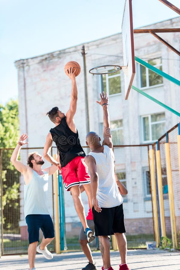 multicultural basketball team playing basketball together royalty free stock photos