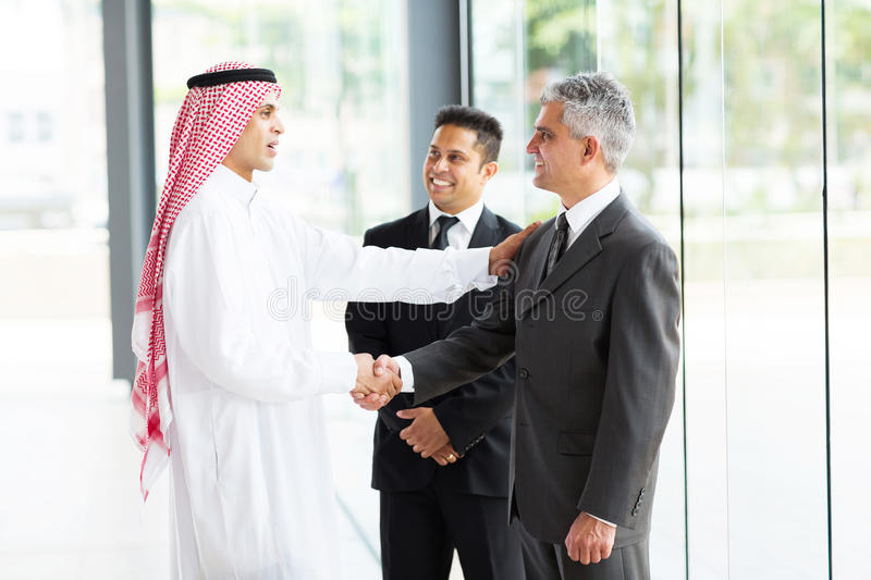 Multicultural business partners handshaking stock photo