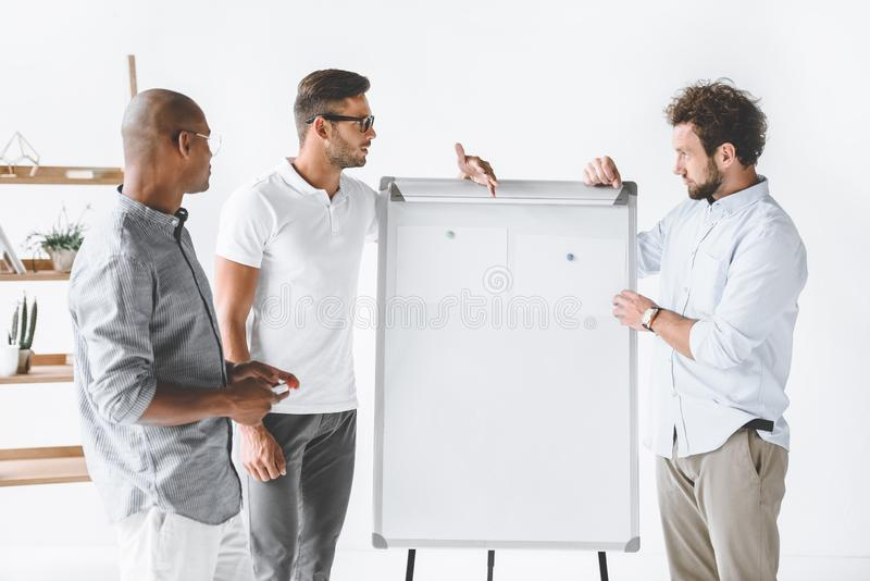 multicultural business people discussing new business strategy at white board stock photo