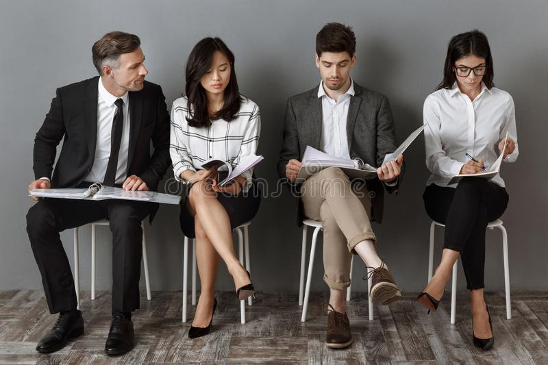 Multicultural business people with folders and notebooks waiting. For job interview royalty free stock image