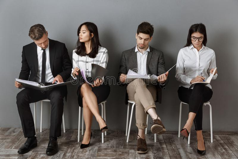 Multicultural business people with folders and notebooks waiting. For job interview stock images