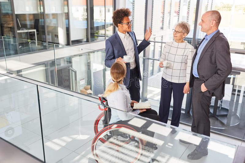 Multicultural business team with colleague in a wheelchair. At a meeting royalty free stock photo