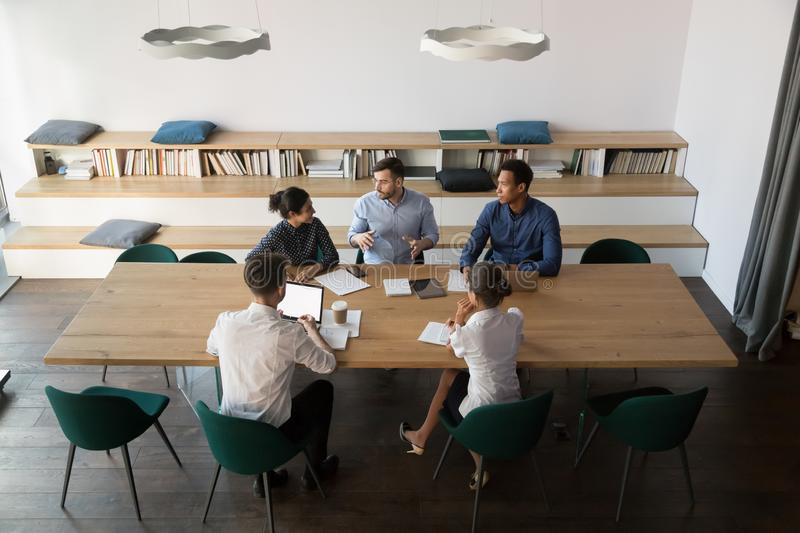 Multicultural business team listening to male boss at group meeting. Multicultural business team people listening to male coach mentor boss at group meeting in royalty free stock photo