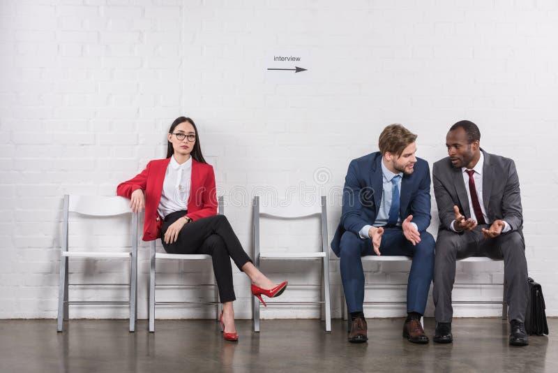 multicultural businessmen having conversation near asian businesswoman stock image