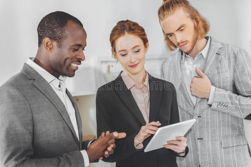 multicultural businesspeople looking at tablet royalty free stock images