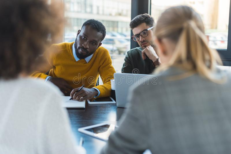 multicultural businesspeople sitting at table royalty free stock photos