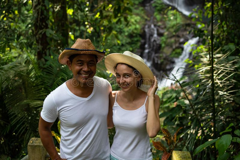 Multicultural couple enjoying waterfall scenery in tropical rainforest. Young mixed race couple on vacation in Asia. Pengibul royalty free stock images