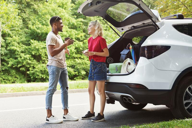 Multicultural couple standing near car royalty free stock photos