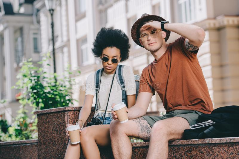 multicultural couple of young tourists sitting royalty free stock images