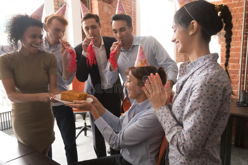 Multicultural employees in party hats congratulate female with birthday cake stock photo