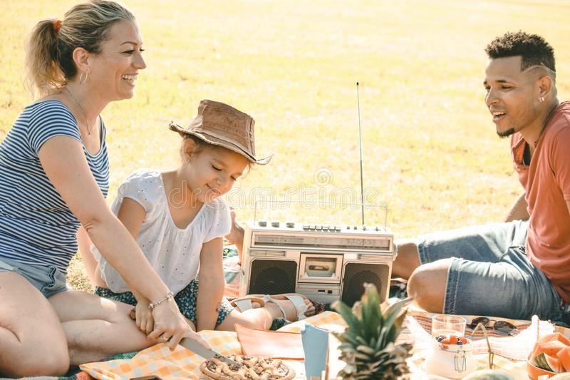 Mixed race family on picnic in park on a sunny day. smiling blond wife cutting a sweet, black husband and cute mixed race child royalty free stock images