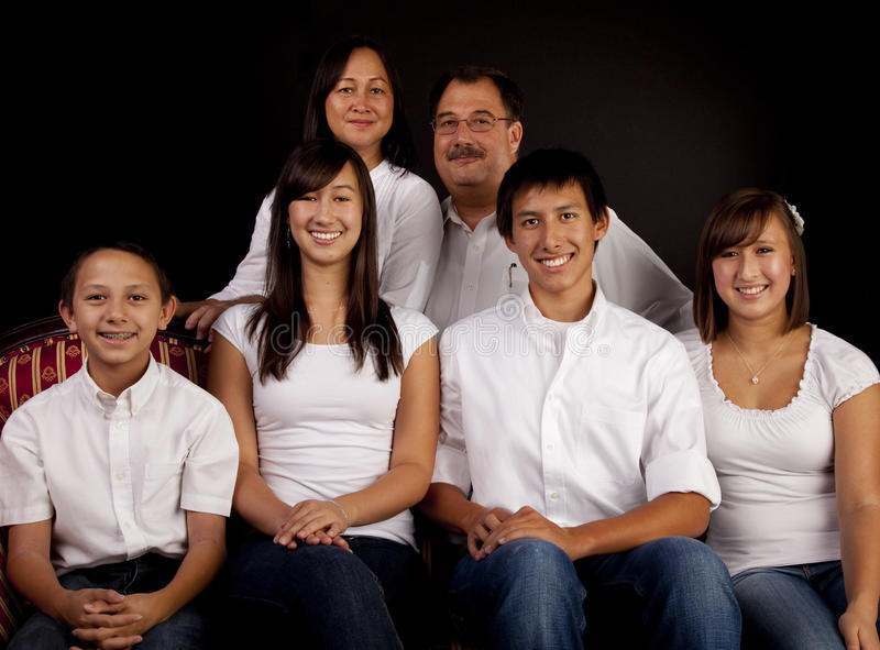 Multicultural Family Portrait. A multicultural American family of six in a seated formal studio portrait with a black background royalty free stock images