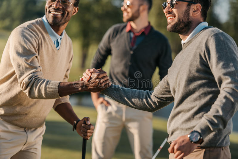 Multicultural friends shaking hands while playing golf on golf course royalty free stock photo